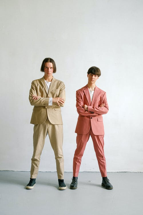 Man in White Suit Standing Beside Woman in Pink Blazer