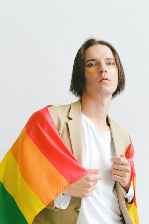 Man With Makeup Holding a Gay Pride Flag