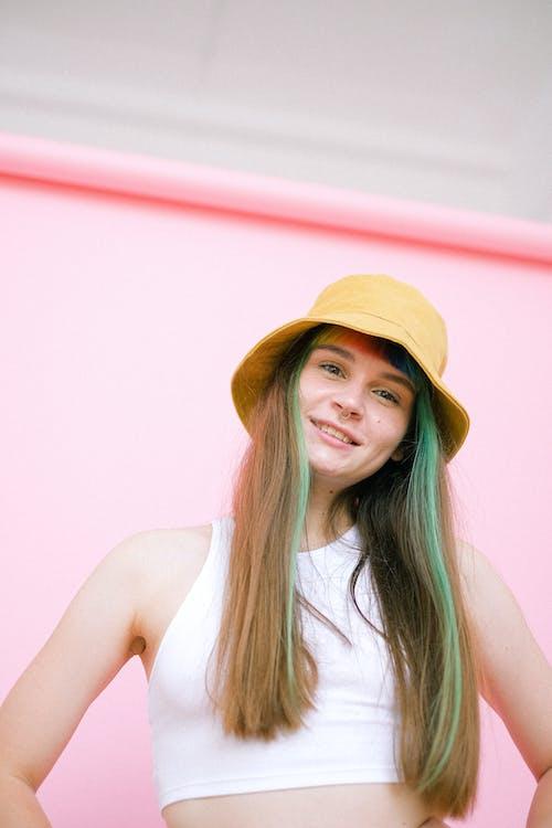 Woman in White Tank Top Wearing Brown Hat