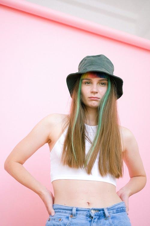 Woman in White Tank Top Wearing Black Hat