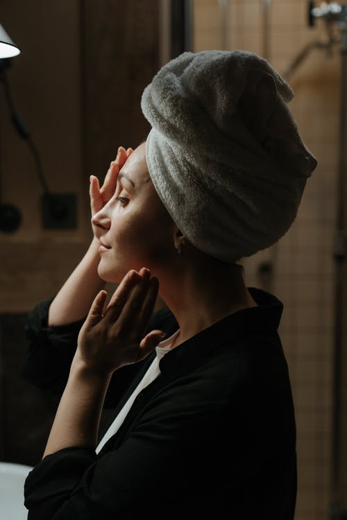 Woman in Black Jacket Covering Her Face With Gray Towel