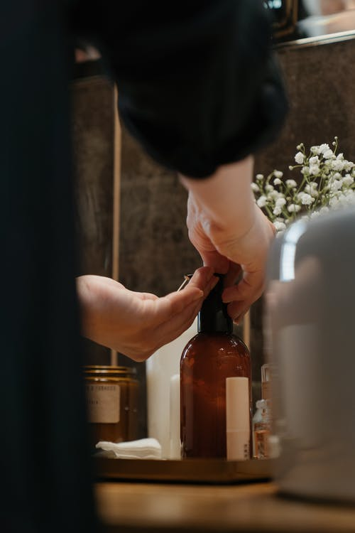 Person Holding Brown Glass Bottle