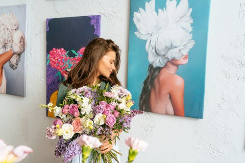 Woman Holding Bouquet of Flowers Beside Paintings