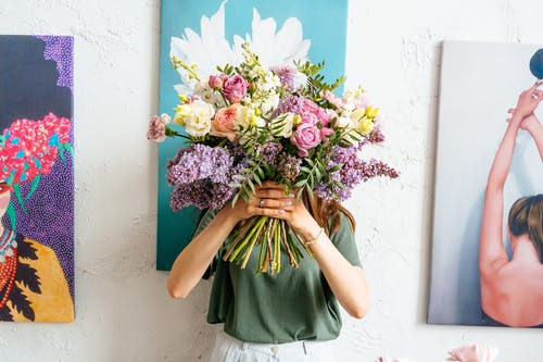 Woman Holding Bouquet of Flowers Covering Her Face
