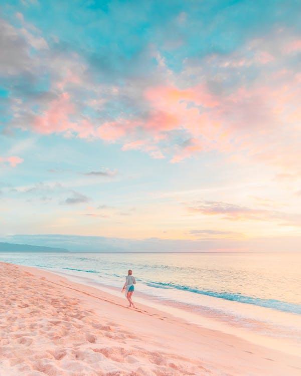 Woman in White Shirt Walking on Beach during Sunset