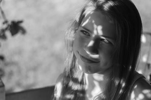 Black and white smiling adolescent girl with shadows on face and body thoughtfully looking away while relaxing at home