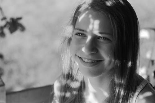 Black and white cheerful teen girl with toothy smile standing in shadow and looking away