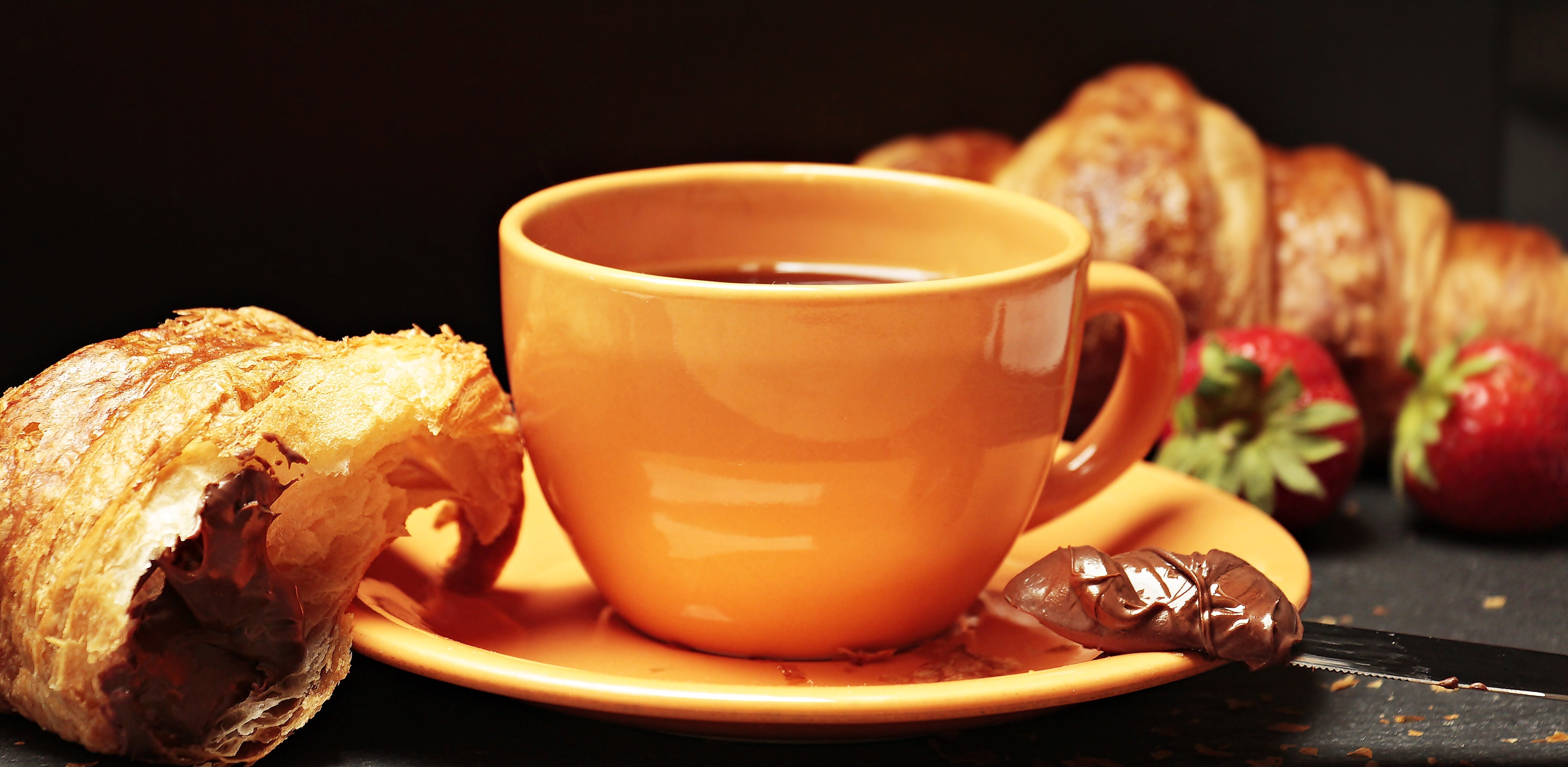 Croissant Near Orange Coffee Cup With Saucer