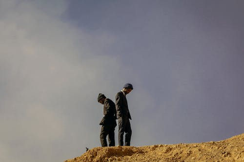 Black men standing on top of hill