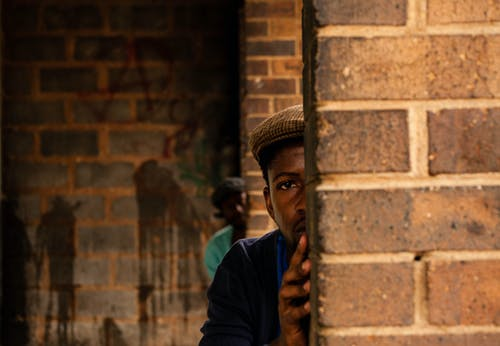 Serious African American males with frightened look hiding behind walls of brick building