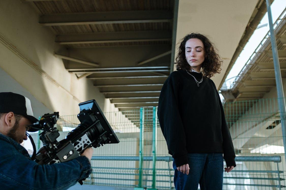 Woman in Black Hoodie Holding Black Video Camera