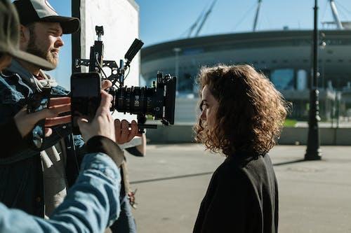 Woman in Black Jacket Holding Black Video Camera