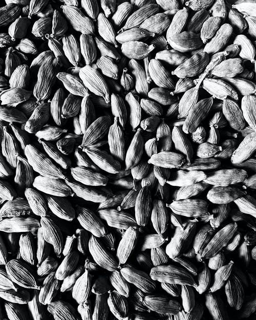 Overhead black and white of textured backdrop representing heap of crunchy cardamon seeds