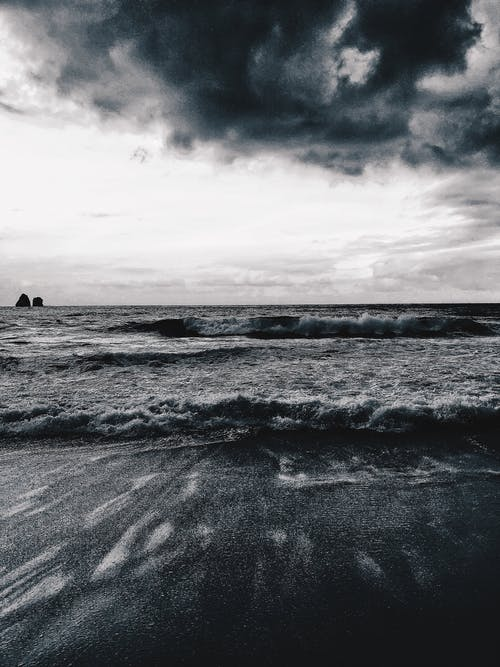 Stormy sea near beach in overcast weather