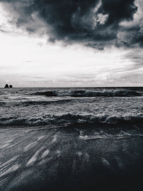 Black and white of wavy ocean near sandy coast under cloudy sky in stormy weather