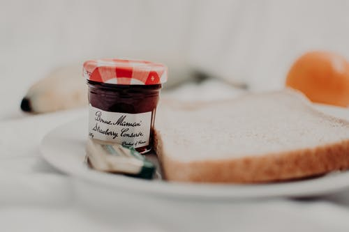 Tasty marmalade in glass jar with written title near bread loaf for breakfast on plate