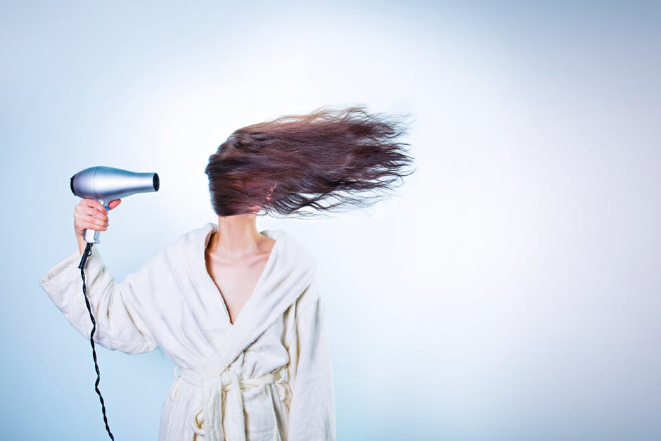 Woman Holding Gray Hair Dryer and Wearing White Bathrobe