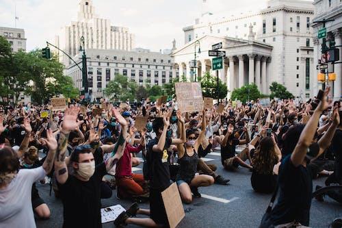 Multidão De Manifestantes Segurando Cartazes E Ajoelhados