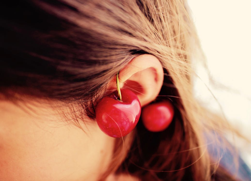 Woman Wearing Red Cherry Earrings