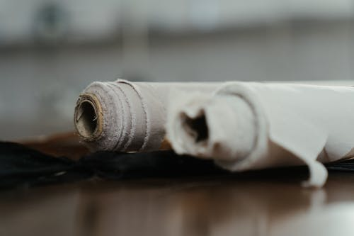 White Thread Roll on Brown Wooden Surface
