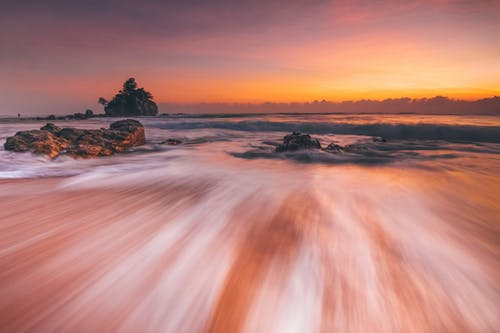 Stormy sea with fast water flow on beach at sunset