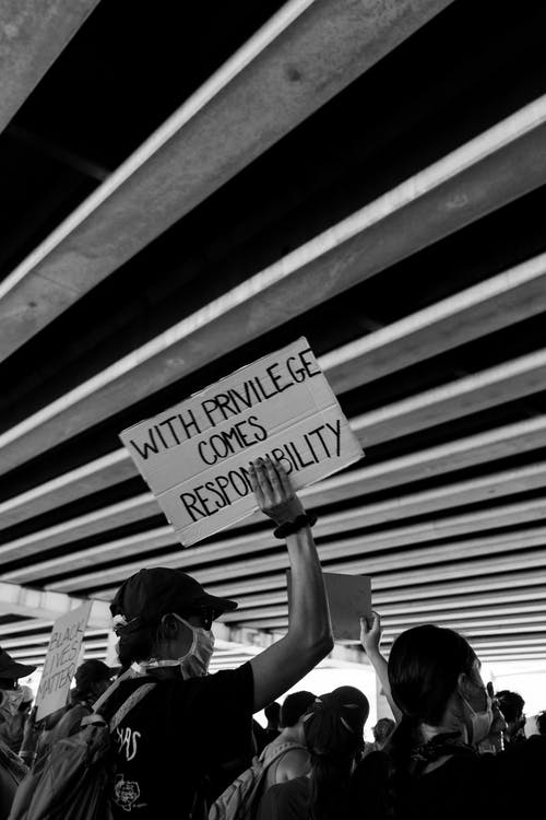 Grayscale Photo of Woman in White Shirt Holding Signage