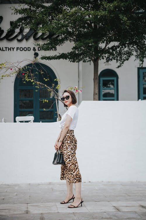 Trendy ethnic woman in sunglasses on street pavement