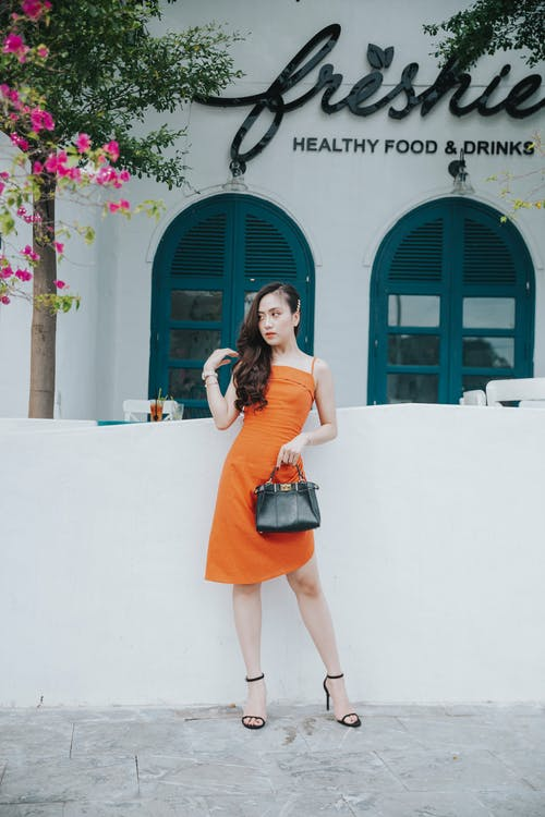 Young trendy ethnic female in colorful apparel with leather handbag touching hair on street near restaurant and looking away