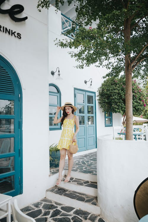 Stylish Asian woman in bright sundress walking on stairs outdoors