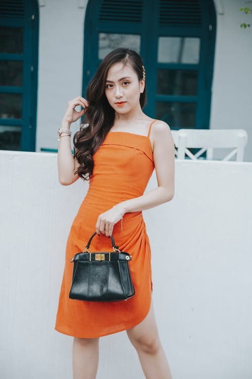 Stylish Asian woman in orange dress with handbag on street