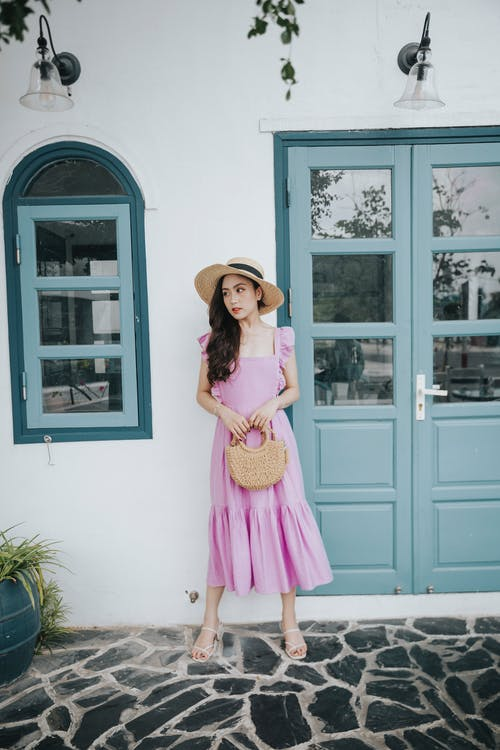 Young wistful ethnic female in purple sundress and straw hat standing with handbag near building and looking away