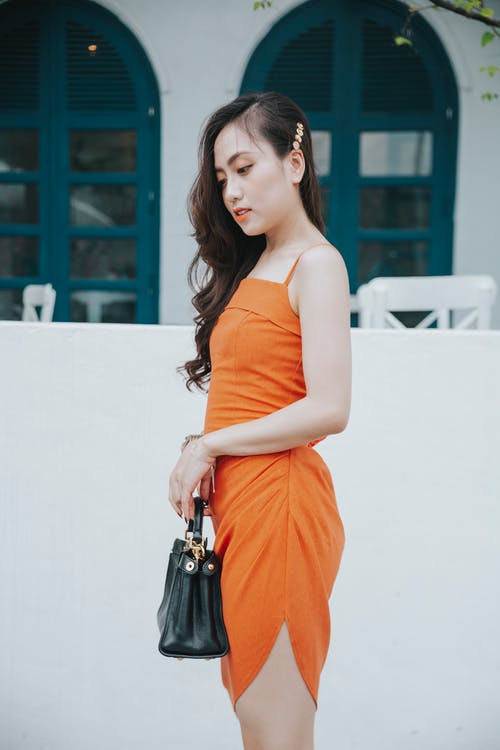 Side view of young pondering ethnic female in colorful wear with modern handbag looking down near fence on street