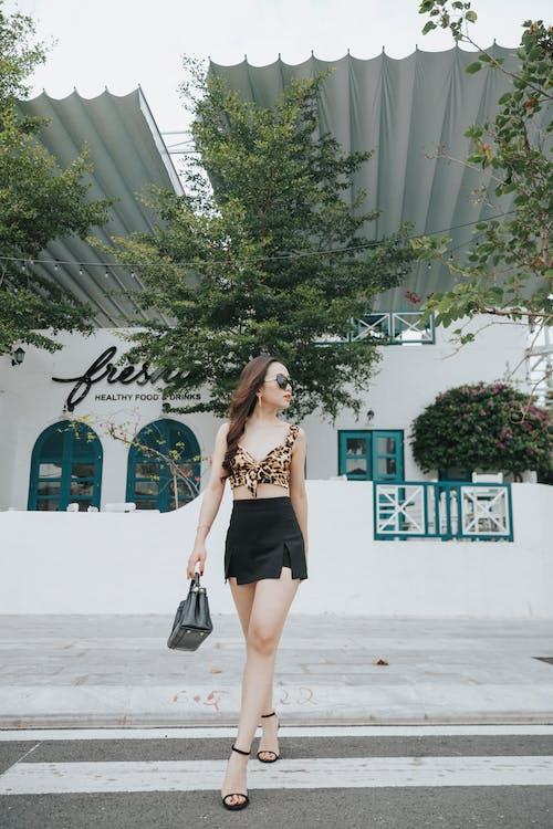 Stylish woman walking on city street