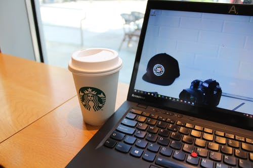Black Lenovo Laptop Beside Starbucks Cup