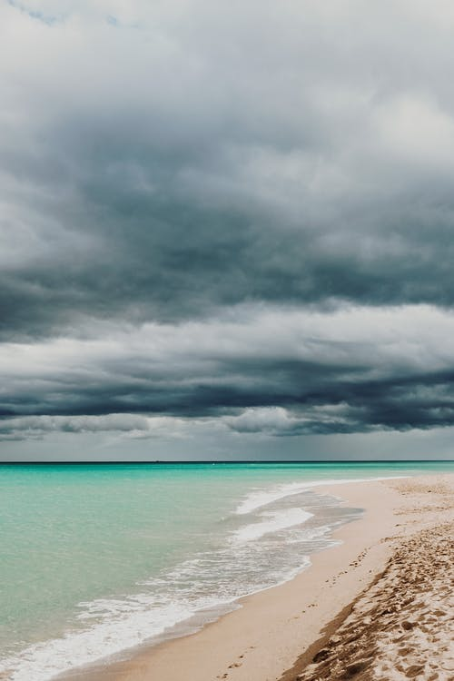 Sandy coast of light blue turquoise bay under grey sky covered with dense clouds