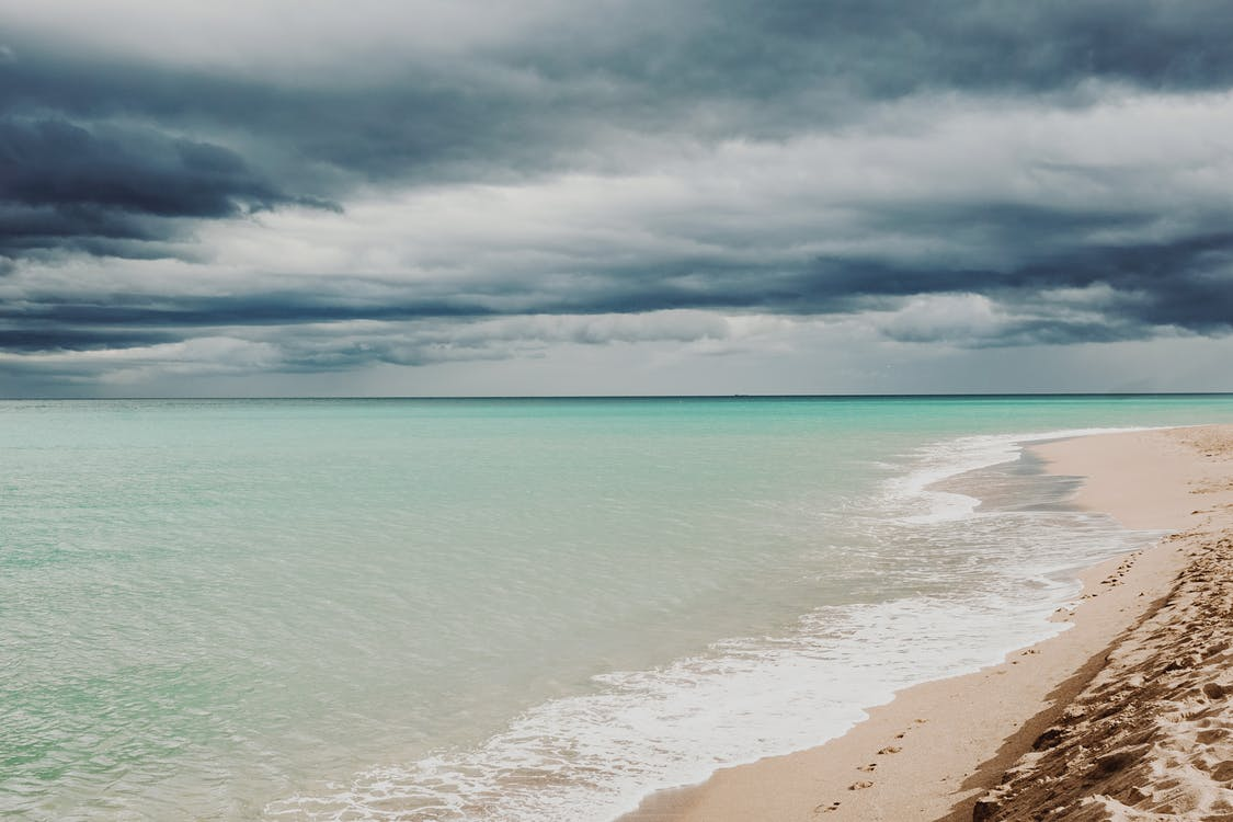 Breathtaking scene of beautiful blue ocean and white sand on shore under cloudy sky