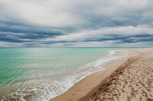 Empty beach with footprints near waving blue sea