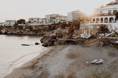 Rocky coast near calm ocean with cliffs and small villas