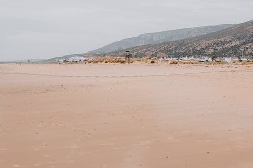 Sandy broad coastline after low tide surrounded by hills