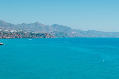 Bright sea near mountains under blue sky