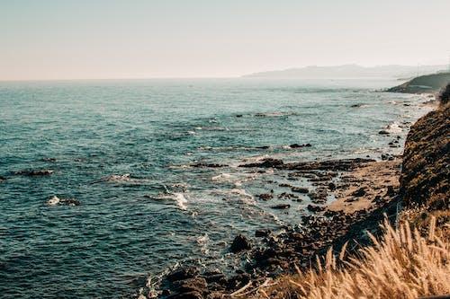 Rocky steep coast of blue sea