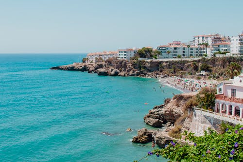City on rocky seashore with tourists on beach