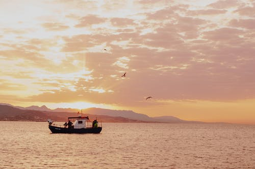 Fishing boat floating on rippling sea in evening