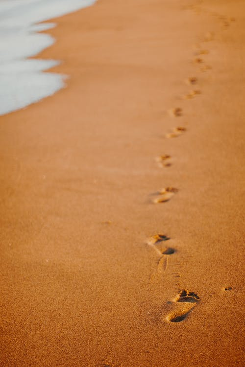 Sandy sea shore with footprints in summer