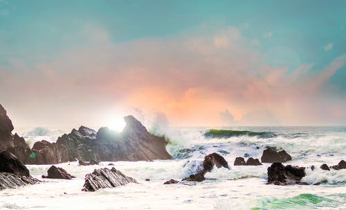 Stormy sea near rocks under sky with bright sunshine