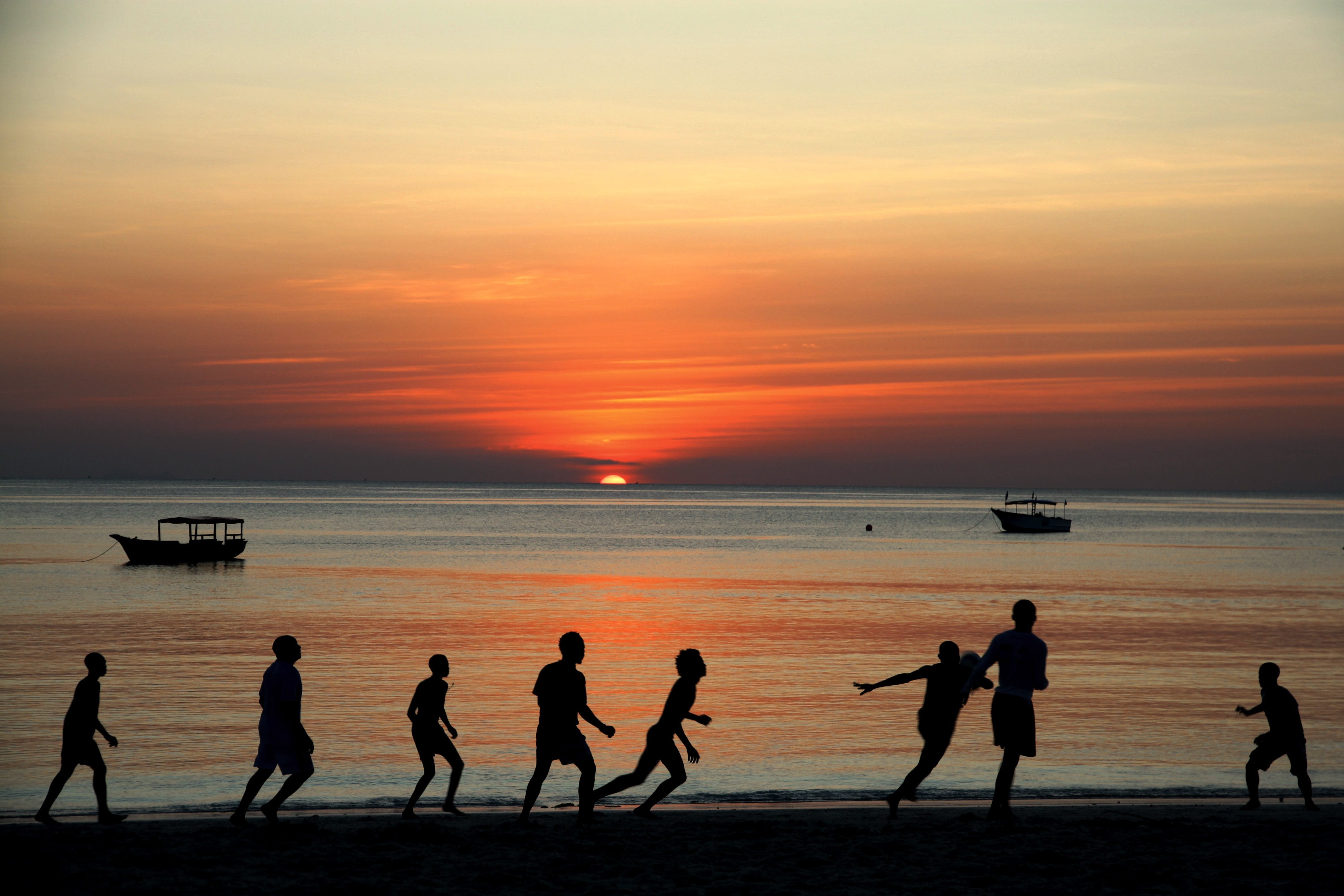 People Playing on Shore during Sunset