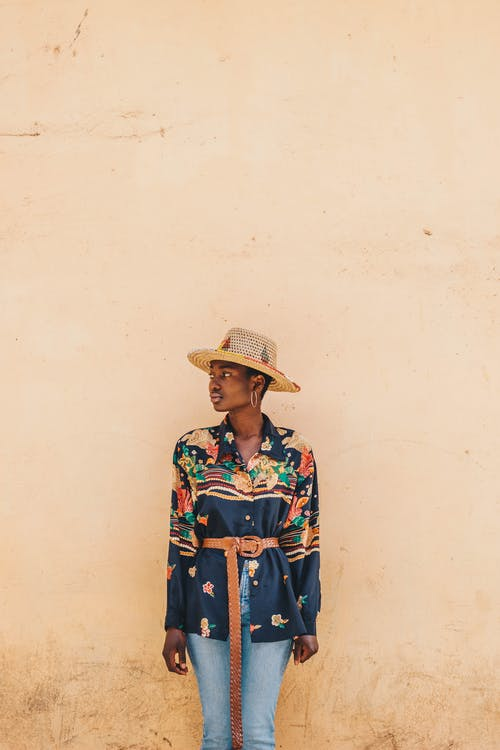 Young trendy African female in ornamental wear with belt and straw hat looking away near rough dirty wall