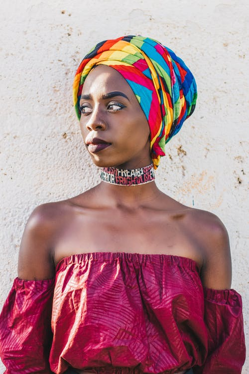 Dreamy black woman in bright headscarf near rough wall
