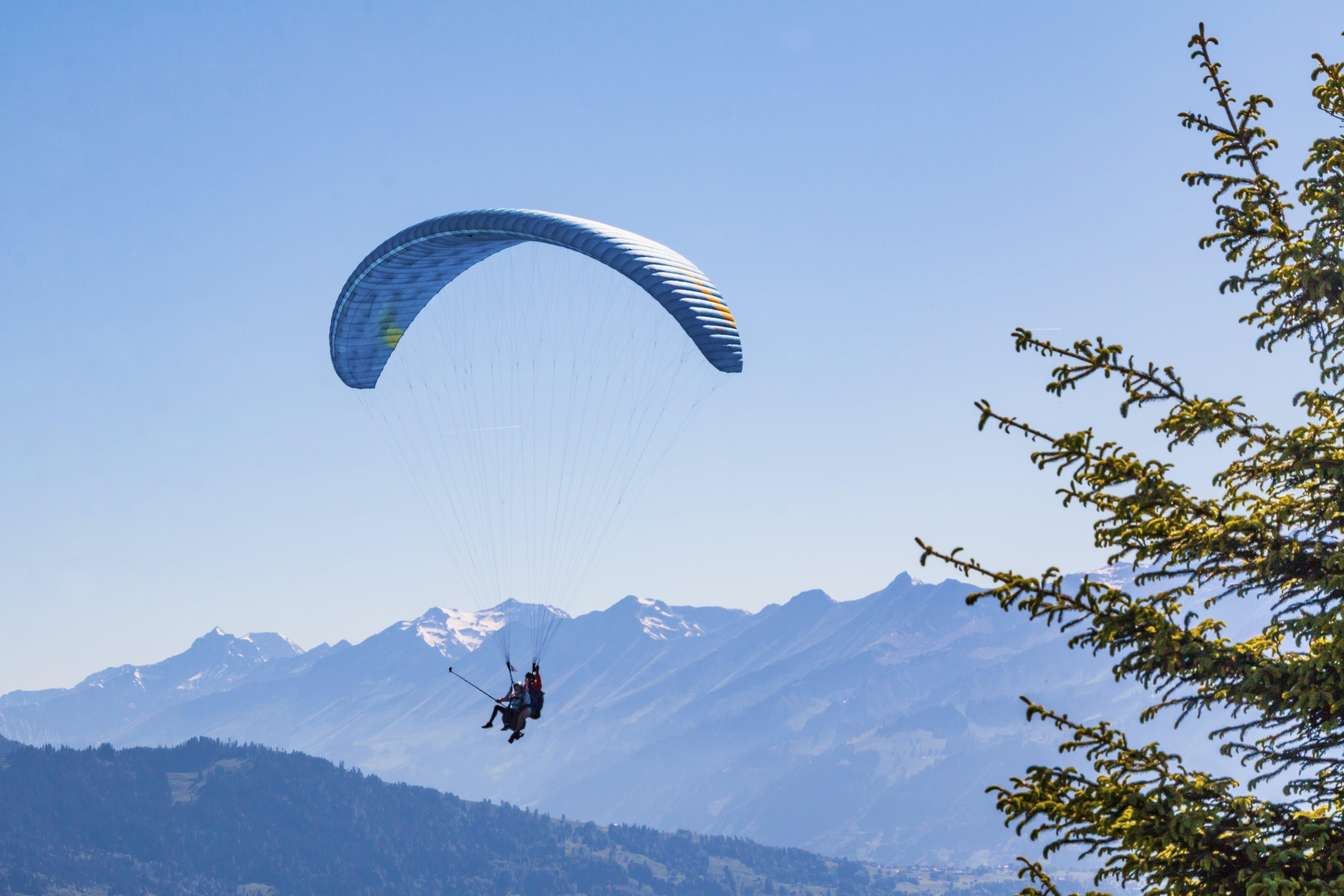 Person Parachuting Under Blue Sky