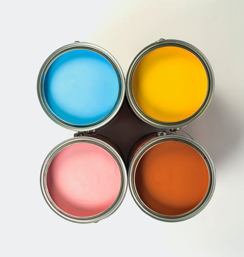 Top view of metal cans with collection of bright paints with smooth surface on white background